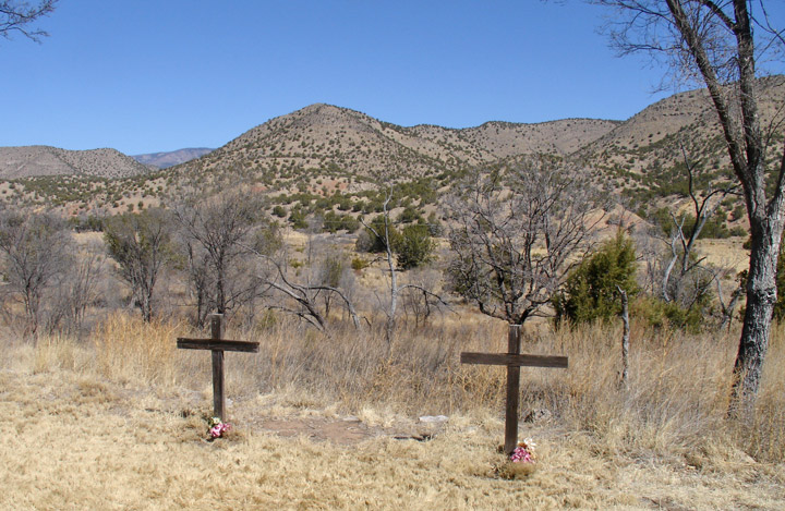 Behind a residence are two graves (Lincoln, New Mexico, USA)